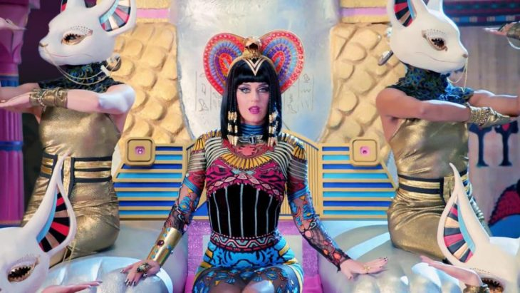 Katy Perry vestida como diosa egipcia con un atuendo de colores y sentada en un trono para la canción Dark Horse