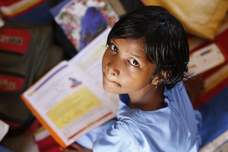 una niña pobre con un libro en las manos voltea a la cámara