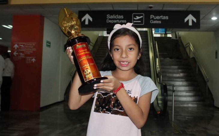 Zury Taplanco en su llegada a Tampico sostiene su trofeo de campeona en Cálculo Mental