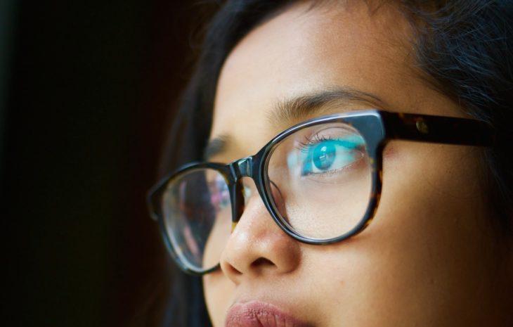 cara de una joven con lentes sobre fondo negro