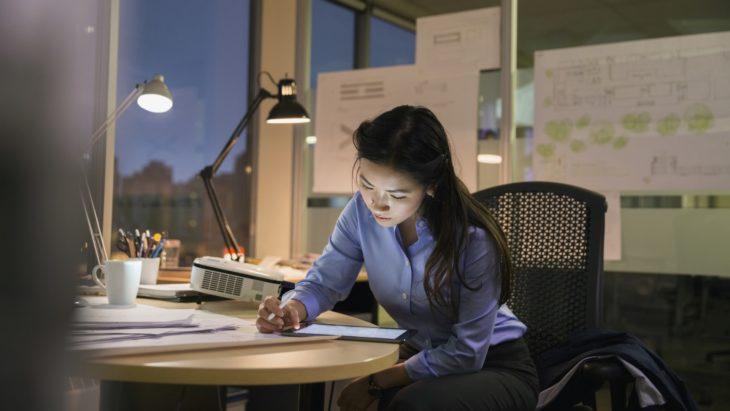 una joven de cabello largo y blusa azul trabaja de noche en una oficina