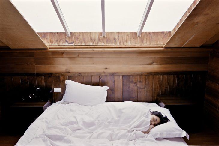 una mujer duerme en una cama con colcha blanca y se observa en la ventana sobre ella la luz del día