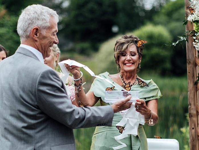 Pareja de adultos mayores sosteniendo un velo con mariposas monarcas reales