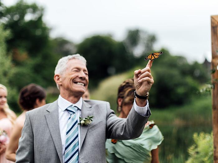 Hombre en un jardín sosteniendo una mariposa monarca en su dedo indice