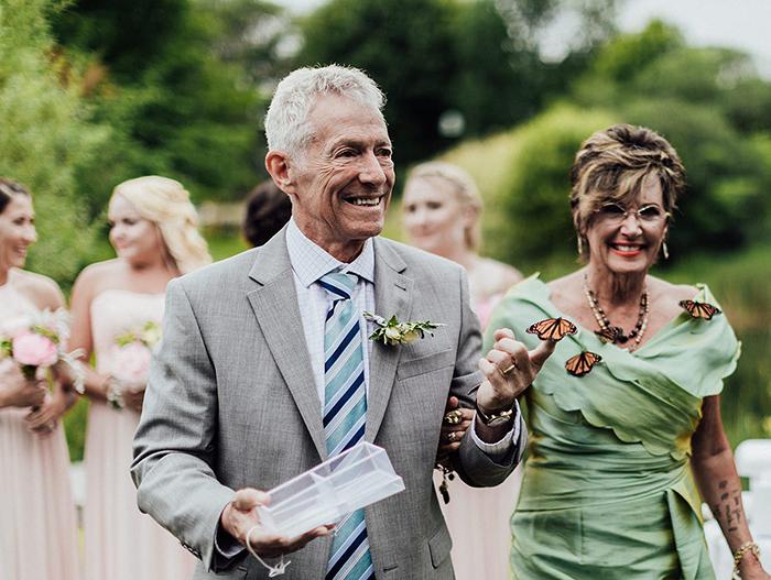 Mujer y hombre caminando en un jardín verdes sosteniendo una mariposa monarca real entre sus manos