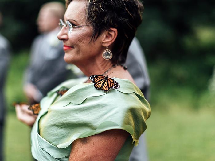 Mariposa monarca sobre el hombro de una mujer en un jardín