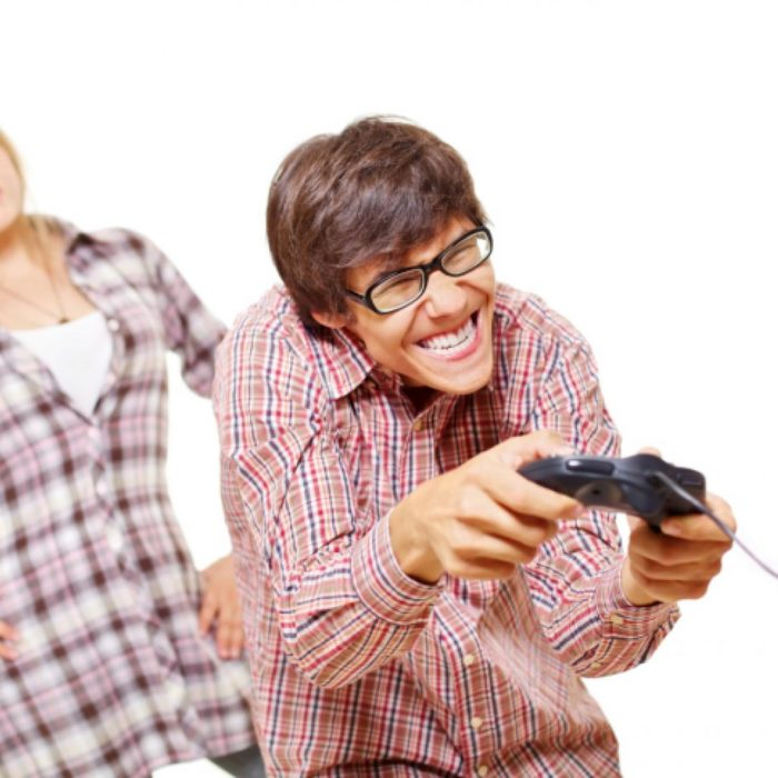 un hombre con lentes y camisa cuadrada juega con un control de consola de juegos y atrás se ve el cuerpo de una mujer que lo mira