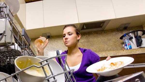 una mujer joven acomoda trastes en una cocina, toma contra picada