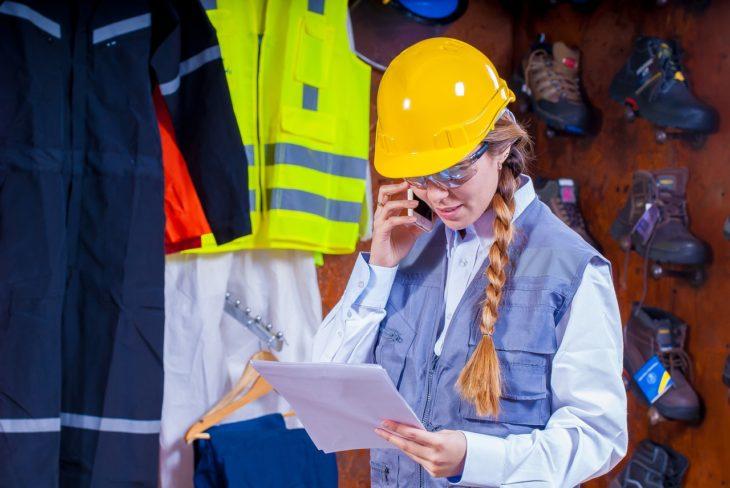 una mujer con casco amarillo y cabello trenzado, con lentes, habla por teléfono mientras ve unos papeles en su mano