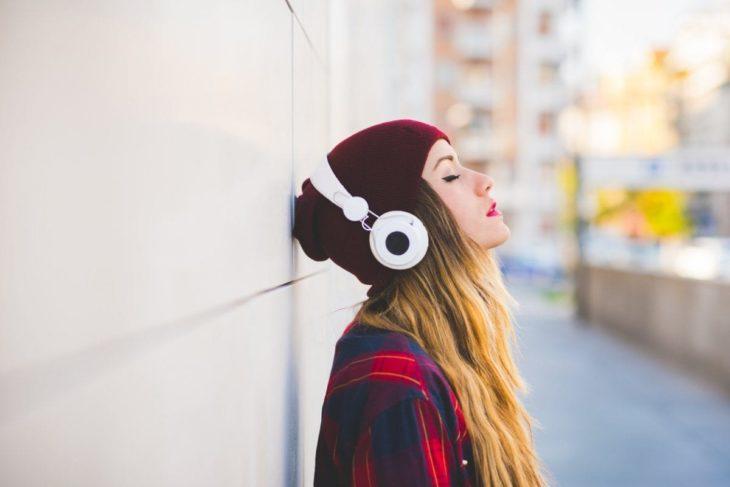 chica rubia cerrando los ojos recargada en la pared escuchando música en audífonos