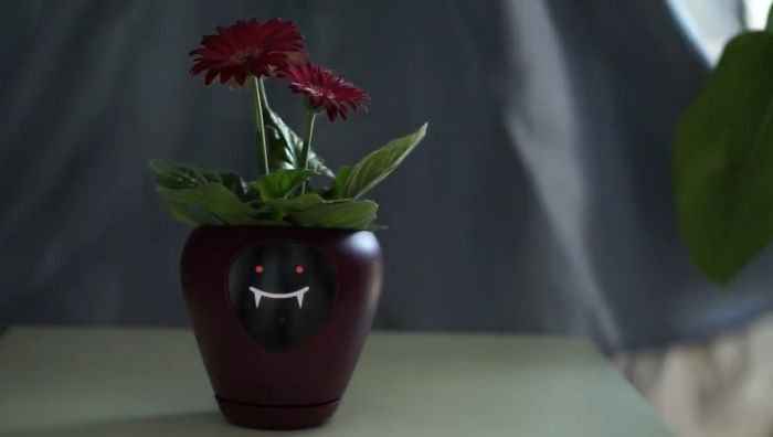 Maceta electronica en tono morado con flores violetas al centro