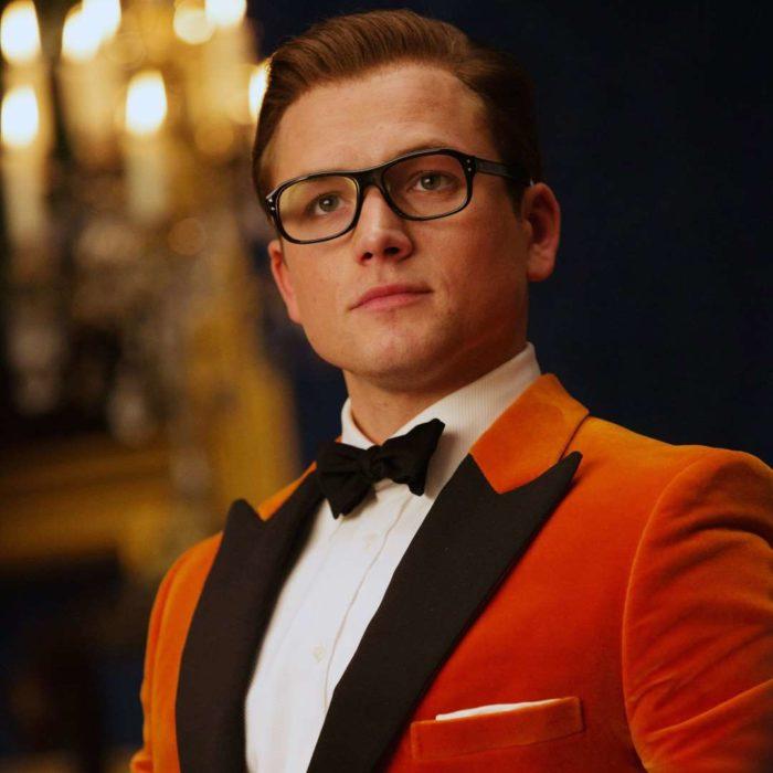 Taron Egerton vestido con saco rojo y moño negro, con lentes