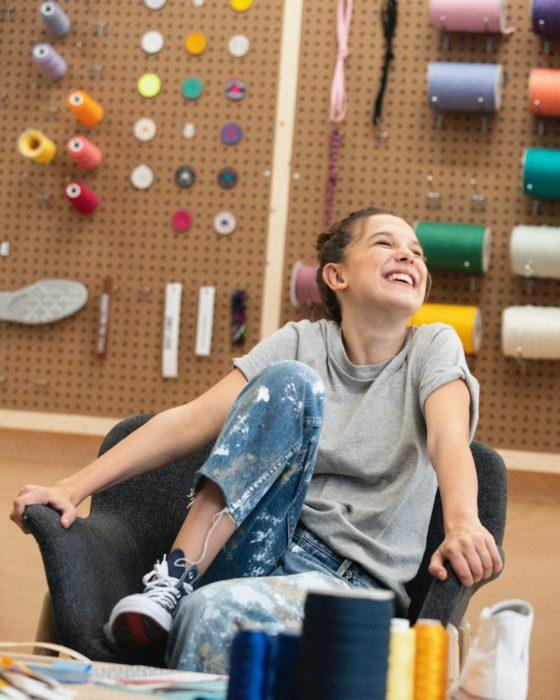 Millie Bobby Brown sentada en una silla, sonriendo