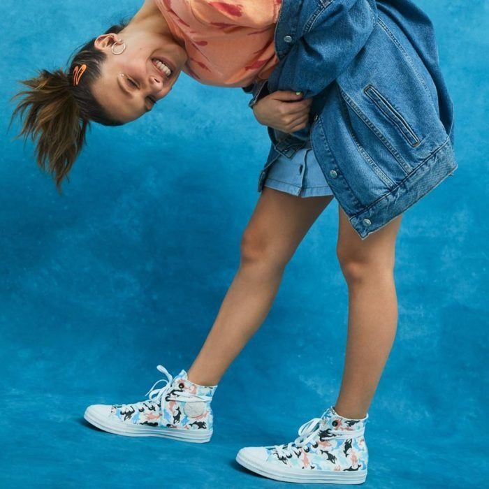 Millie Bobby Brown agachada mostrando sus tenis converse