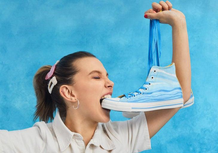 Millie Bobby Brown comiendo un teni converse en tono azul cielo