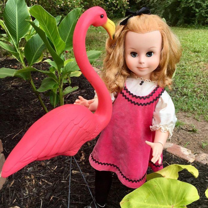 Madeline y Malachi Dressel; muñeca vintage con vestido rosa y cabello rubio en el jardín junto a un flamenco de adorno