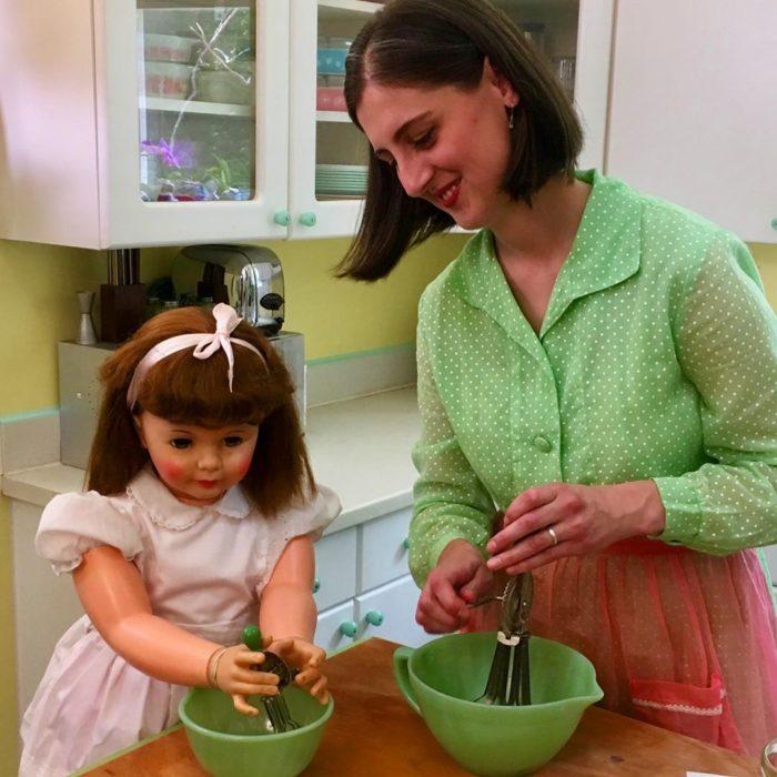 Madeline y Malachi Dressel; mujer cocinando con su muñeca vintage de tamaño real