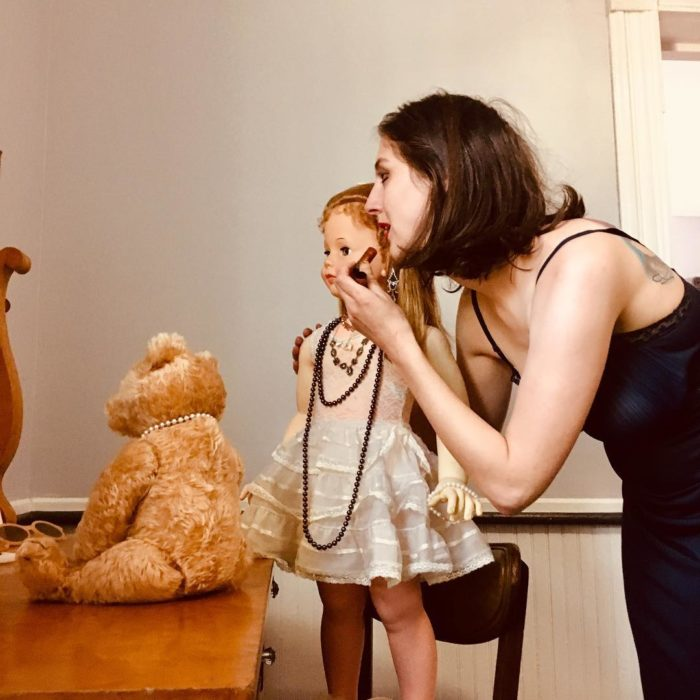 Madeline y Malachi Dressel; mujer maquillándose frente a espejo junto con muñeca vintage de tamaño real