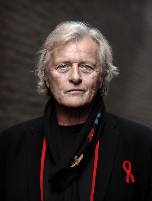Rutger Hauer vestido de negro y con listón rojo contra el SIDA