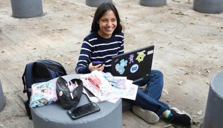 Nataly sonriendo con su computadora y papeles escolares