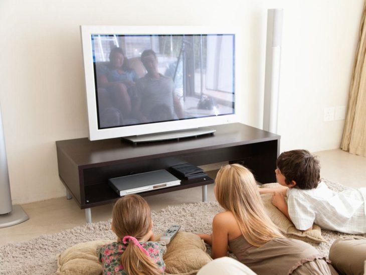 dos niñas y un niño ven la televisión acostados en una sala