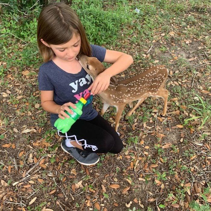 Laurie, la niña que habla con los animales como Eliza Thornberry; pequeña alimentanto con biberón a cervatillo