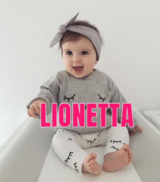 Bebé usando moño gris en la cabeza, sentada sobre un colecho