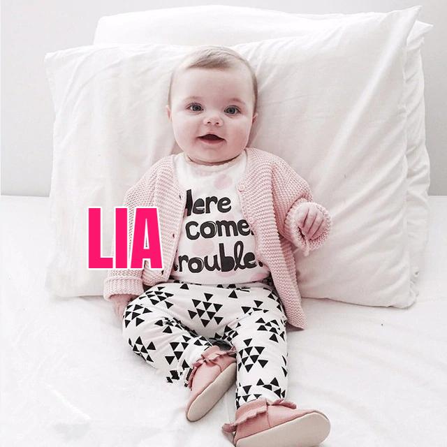 Niña recostada en una almohada sobre su cama, usando suéter rosa pastel