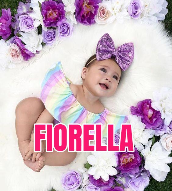 Niña recostada sobre una alfombra blanca rodeada de flores lilas