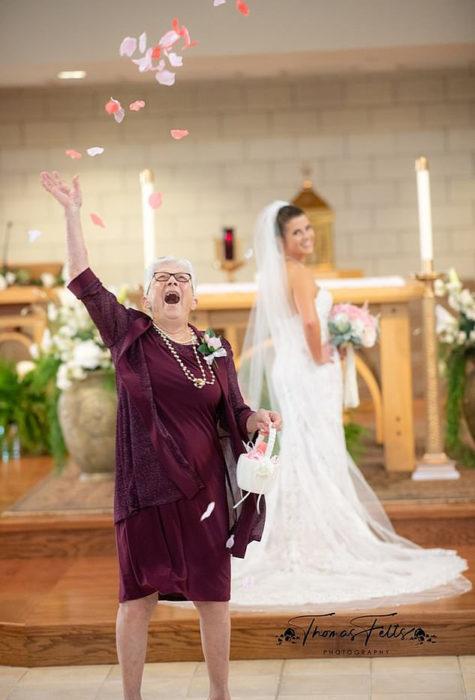 Abuela lanzando pétalos mientras su nieta está posando para las fotos de su boda