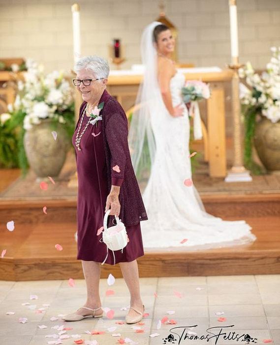 Abuela lanzando pétalos mientras su nieta camina hacia el altar
