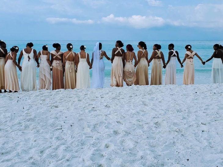 Novia posando junto a sus 34 damas de honor el día de su boda en la playa, vestidas en color nude