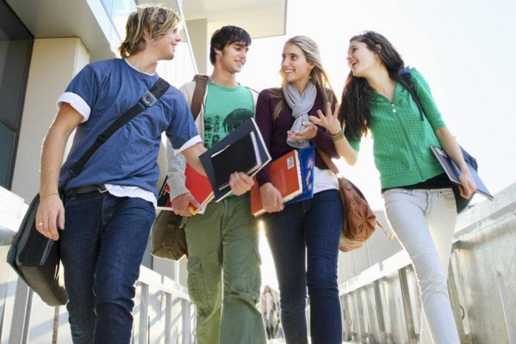 un grupo de cuatro estudiantes adolescentes caminando por un pasillo