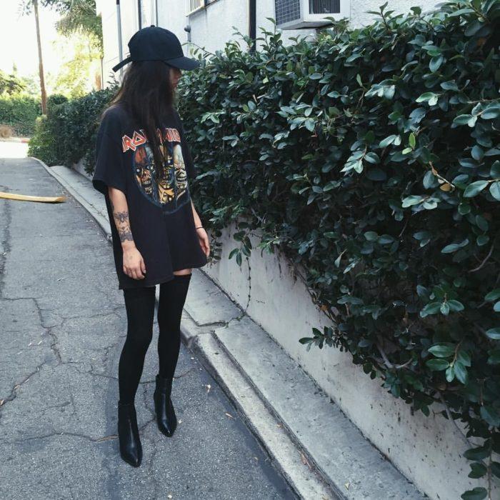 Mujer con playera rockera de Iron Maiden como vestido, medias largas y cachucha, con tatuajes en los brazos