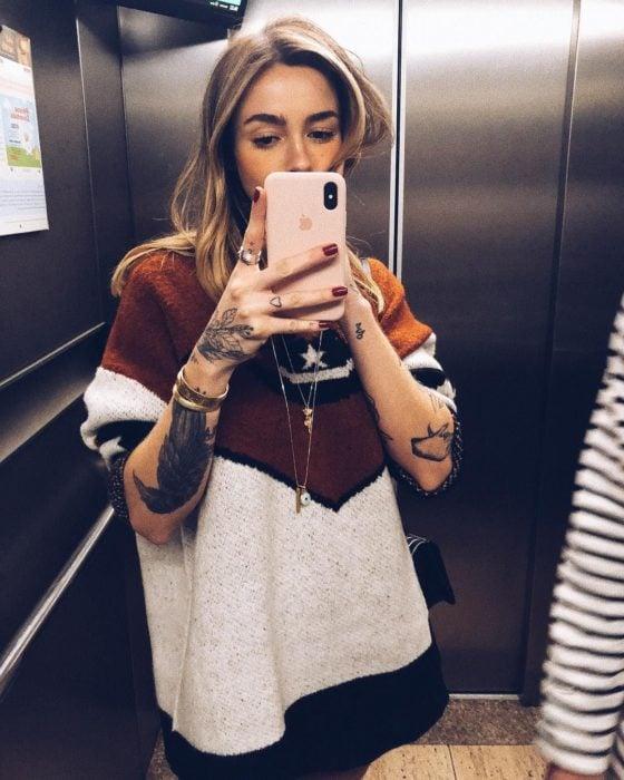 Chica rubia tomándose selfie en espejo del elevador; con suéter tejido oversized, con tatuajes en los brazos y manos