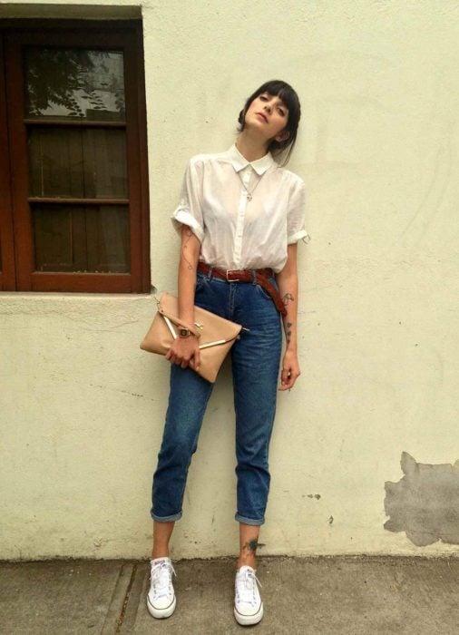 Chica recargada en la pared, con camisa blanca formal, bolsa beige de mano, jeans y tenis blancos; tatuajes en los brazos