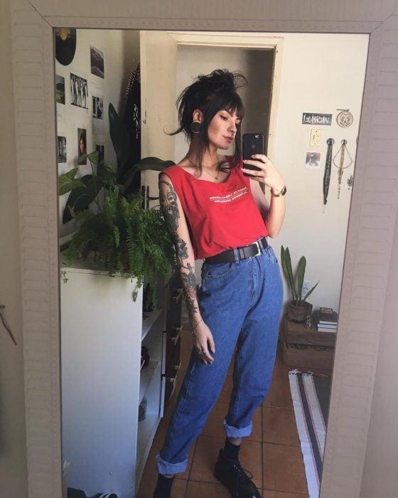 Chica vestida con estilo grunge, playera sin mangas, mommy jeans, expansiones en las orejas y tatuajes en los brazos