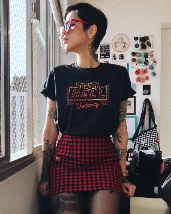Chica con cabello negro y corte pixie, con lentes retro rojos, playera con estampado y falda de cuadros negros y rojos, look estilo noventero, con tatuajes en los brazos y piernas