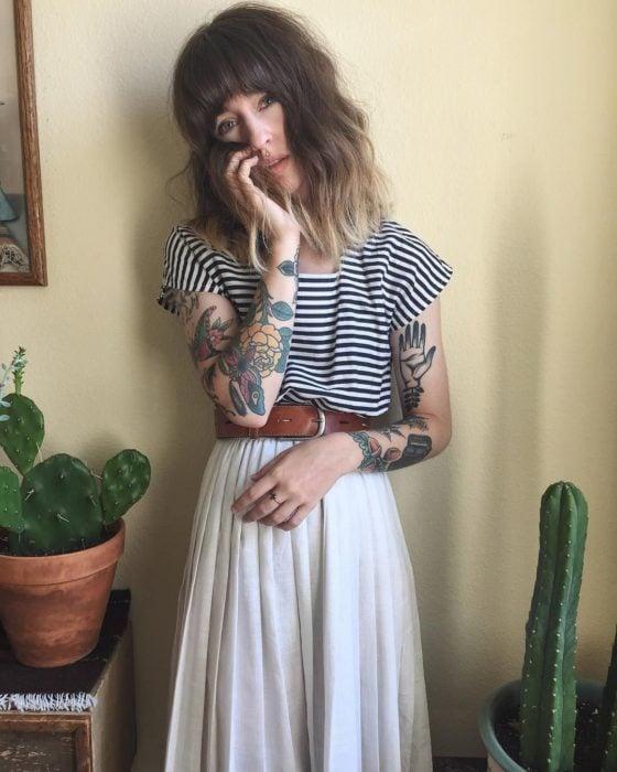 Chica con look estilo boho, cabello a los hombros con degradado ombré, blusa de rayas horizontales, falta blanca y larga, con cinto; tatuajes old school en los brazos; macetas con cactus