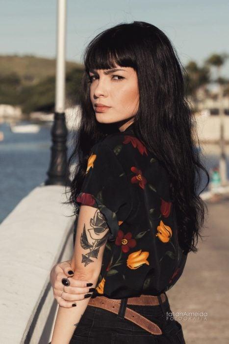 Chica de espaldas, con cabello largo, negro y con fleco, piercing en la nariz y tatuaje en el brazo; camisa negra con flores