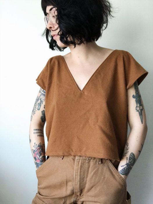Chica con cabello de honguito color negro, con lentes retro, blysa café y tatuajes en los brazos
