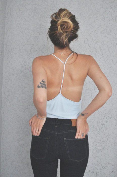 Choca con peinado chongo, blusa blanca sin espalda y tatuaje en el antebrazo