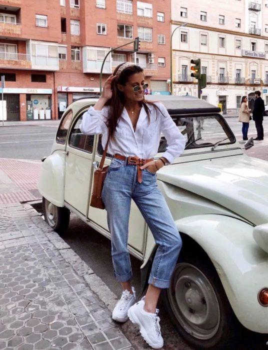 Chica usando un pantalón de mezclilla hasta los tobillos, blusa de color blanco y uglye sneakers