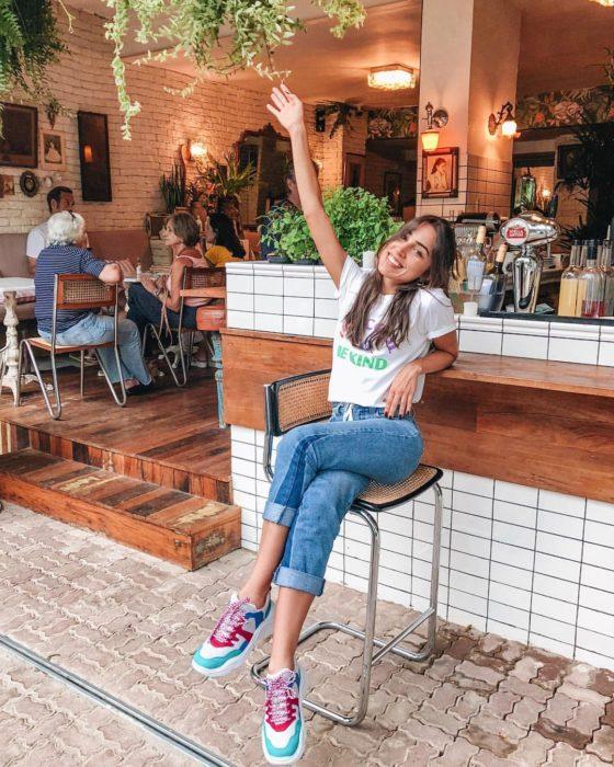 Chica usando jeans, blusa blanca y tenis ugly de colores