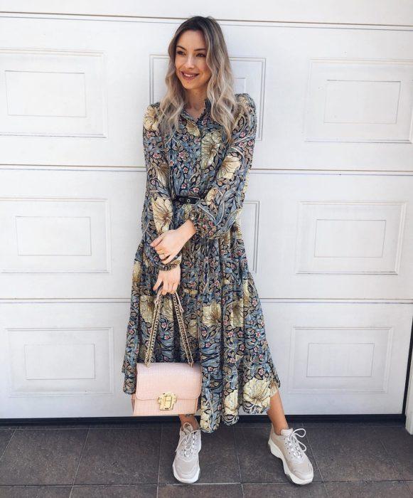 Chica parada afuera de su casa usando un vestido de color gris y en sus manos sujetando un bolso de color rosa y con unos ugly sneakers de color tierra