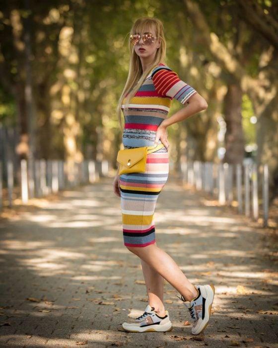 Chica usando un vestido de rayas horizontales conn unos ugly sneakers de colores tierra mientra está posando para una foto
