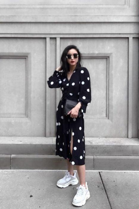 Chica usando un vestido de color negro con puntos blancos y unos ugly sneakers en color blanco