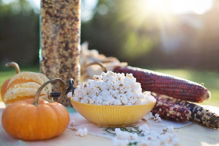 palomitas de maíz en un plato amarillo al lado de unas mazorcas de maíz sobre una mesa