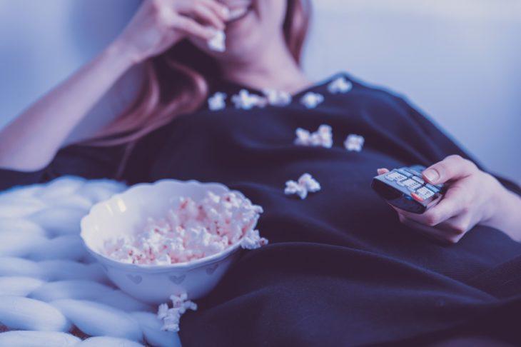 el cuerpo de una mujer se ve sobre una cama en donde come palomitas de maíz