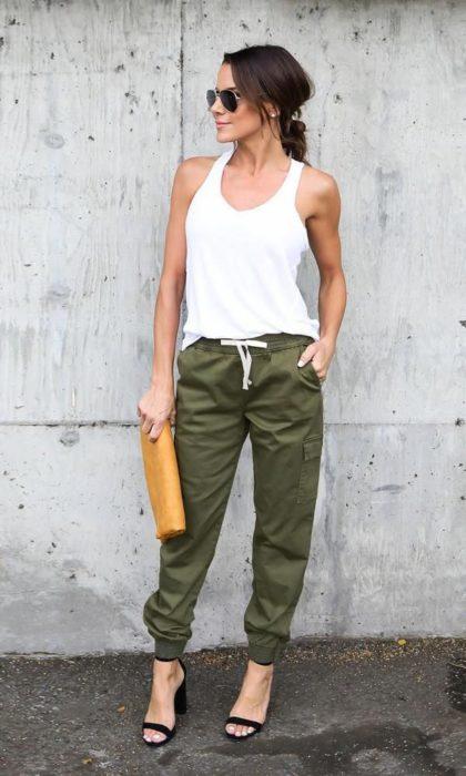 Chica usando un pantalón jogger de color verde militar con una blusa de tirantes de color blanco